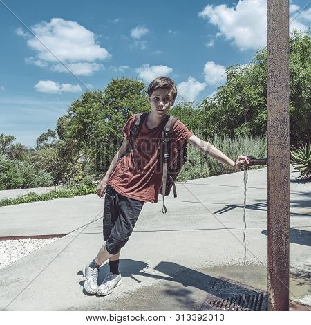 Teen Boy With Backpack Leaning On A Faucet In A Park