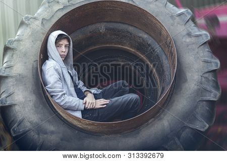 Portrait Of A Young Man Sitting In A Huge Wheel Of A Tractor