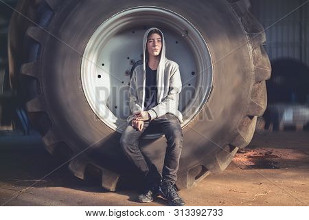 Portrait Of A Smiling Young Man Sitting In A Huge Wheel Of A Tractor
