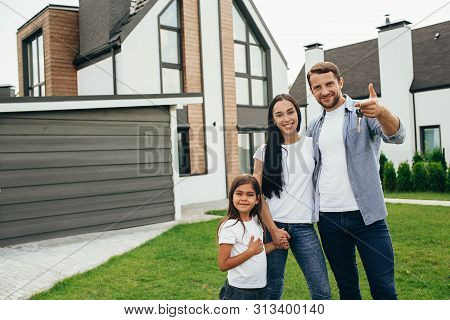 Happy Family Mother Father And Child Standing Near Their New House. Man Holding Keys From New Apartm