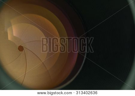 Beautiful Camera Lens  With Yellow Light Of Glass On A Black Background.