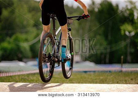 Back Young Cyclist Riding Springboard On Mountainbike