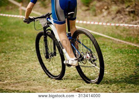 Back Woman Mountain Biker Riding Green Grass On Mountainbike