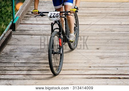Female Cyclist Athlete Descent Wooden Bridge On Mountainbike Starting Number