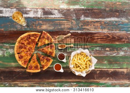 Fresh Italian Pizza And Crispy French Fries Served On Rustic Wood Table, With Ketch Up,chili Sauce,