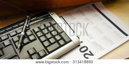 Keyboard, Pen And Calendar On The Table. Workplace