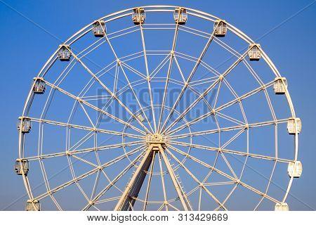 Ferris Wheel In Summer On Blue Sky Amusement Park