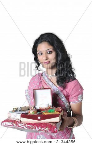 Close up of a beautiful Indian lady holding a plate full of traditional gifts. poster