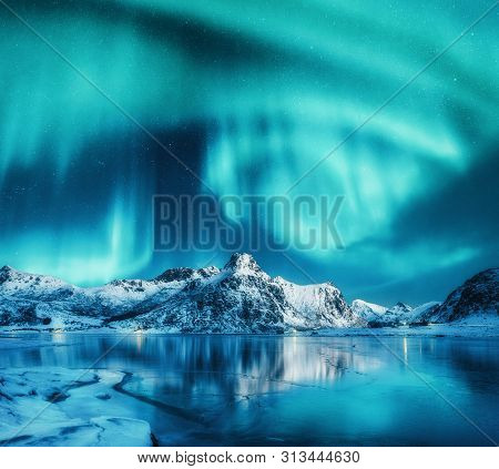 Aurora Borealis Above Snowy Mountains, Frozen Sea Coast And Reflection In Water In Lofoten Islands,