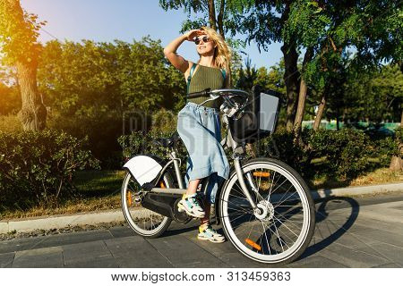 Full-lenght Photo Of Blonde In Sunglasses Looking At Side In Long Denim Skirt Standing On Bike Next