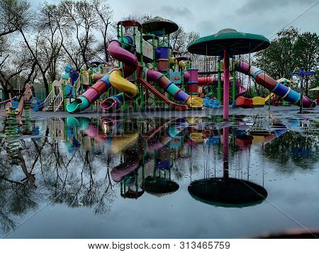 Empty Children Playground After Rain. Playground Mirroring In A Plash /pool
