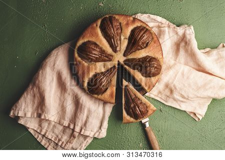 Tasty Fruitcake With Pears On A Kitchen Towel. Above View With Pear Tart On A Green Table