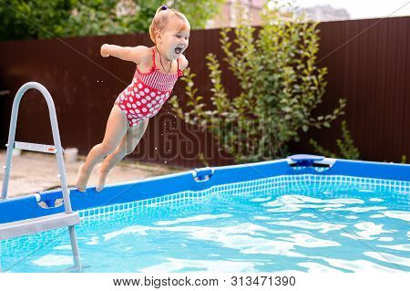 Happy Little Girl In Red Swimsuit Jumping Into Outdoor Swimming Pool At Home. Baby Girl Learning To