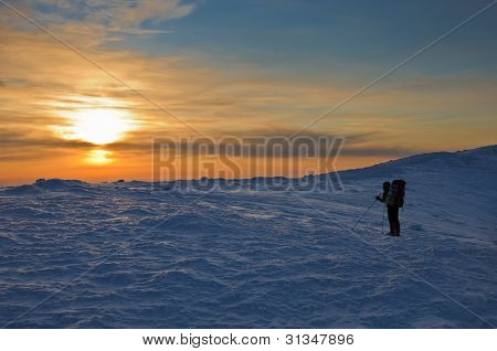 Trekker Silhouette At Sunset In The Mountains