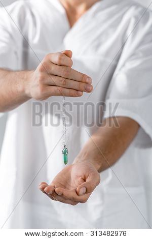 Cropped View Of Hypnotist Holding Green Stone In Clinic