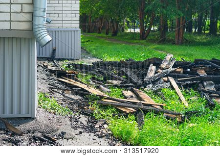 The Black Charred Rafters, Roof Framework, Nails Sticking Out, Debris on the Lawn near the Apartment Building with Downspout After the Fire. Insurance Concept. poster
