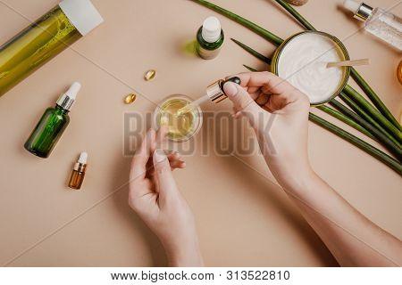 Woman Cosmetologist Cosmetics Testing. Natural Organic Cosmetics. Serum Hair Mask. Flat Lay Pastel