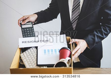 Businessman prepared will being sending resignation letter to company and carrying packing belongings and files into brown cardboard box, changing and resigning from work concept. poster