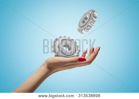 Side Closeup Of Womans Hand Facing Up And Levitating Two Metal Cogwheels On Light Blue Gradient Back