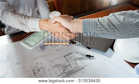 Architect And Engineer Construction Workers Shaking Hands While Working For Teamwork And Cooperation