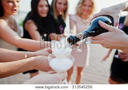 Group Of 8 Girls Wear On Black And 2 Brides At Hen Party Against Sunny Beach Drinking Champagne.