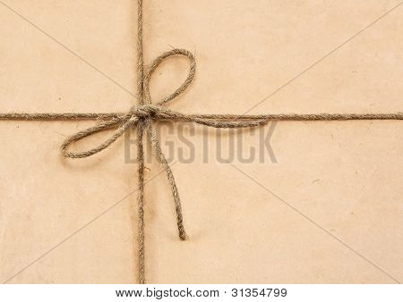 String tied in a bow on a brown recycled paper poster