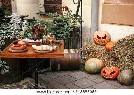 Pumpkins With Scary Faces On Hay At Cafe Table, Holiday Decoration Of Store Fronts And Buildings. Ha