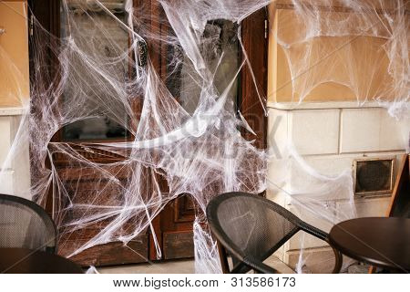 Spooky Spider Web On Building Facade In City Street, Holiday Decoration Of Store Fronts. Halloween S