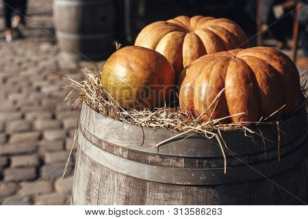 Pumpkin On Barrel With Hay In City Street, Holiday Decorations Store Fronts And Buildings. Halloween