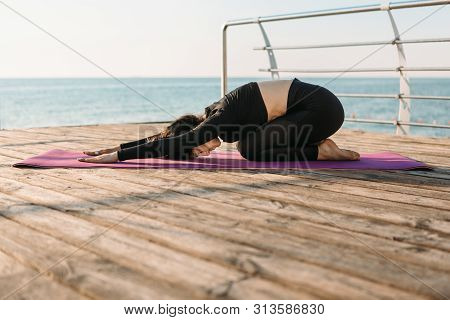 Young Brunette Woman In A Black Jumpsuit Practicing Yoga Stretching Exercises On The Beach At Sunris