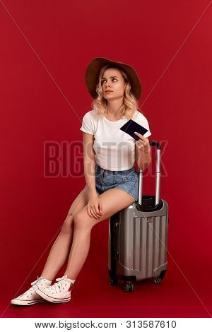 Exhaust Young Woman With Blod Curly Hair In A Sundown Hat Sits On A Grey Luggage Bag Holding Passpor