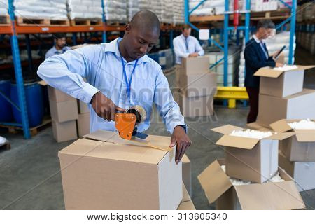 Front view of handsome mature African--american male staff packing cardboard box with tape gun dispenser in warehouse. This is a freight transportation and distribution warehouse. Industrial and