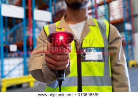 Mid section of mature Asian male worker showing barcode scanner on camera in warehouse. This is a freight transportation and distribution warehouse. Industrial and industrial workers concept