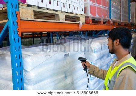 Side view of mature Asian male worker scanning package with barcode scanner in modern warehouse. This is a freight transportation and distribution warehouse. Industrial and industrial workers concept