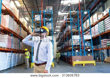 Front view of handsome mature Caucasian male supervisor using virtual reality headset in warehouse. This is a freight transportation and distribution warehouse. Industrial and industrial workers poster