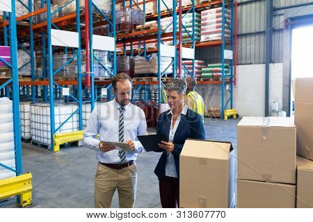 Front view of mature Caucasian staffs working together in warehouse. African-american warehouse worker standing in yellow vest behind supervisors. This is a freight transportation and distribution poster
