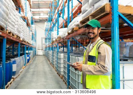 Front view of happy mature Asian male worker holding digital tablet and looking at camera in warehouse. This is a freight transportation and distribution warehouse. Industrial and industrial workers