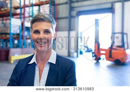 Portrait close-up of beautiful mature Caucasian female manager looking at camera in warehouse. This is a freight transportation and distribution warehouse. Industrial and industrial workers concept