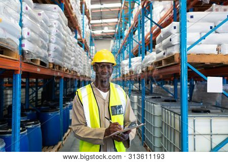 Portrait happy mature African-american male worker looking at camera while writing on clipboard in warehouse. This is a freight transportation and distribution warehouse. Industrial and industrial