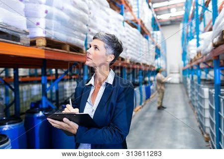Front view close-up of beautiful mature Caucasian female manager checking stocks on clipboard in warehouse. This is a freight transportation and distribution warehouse. Industrial and industrial