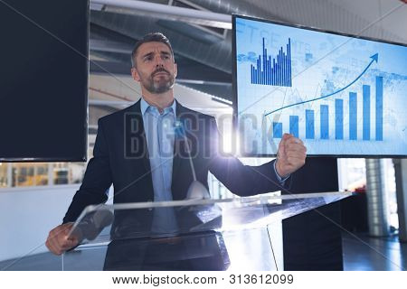 Front view of caucasian Male speaker speaking at podium in business seminar at conference meeting. International diverse corporate business partnership concept