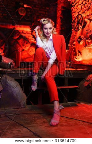 Full-lenght photo of young blonde girl in red jacket looking at camera in nightclub
