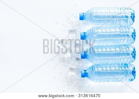 Cold Pure Water In Plastic Bottles With Ice Cubes On White Background Top View Mockup