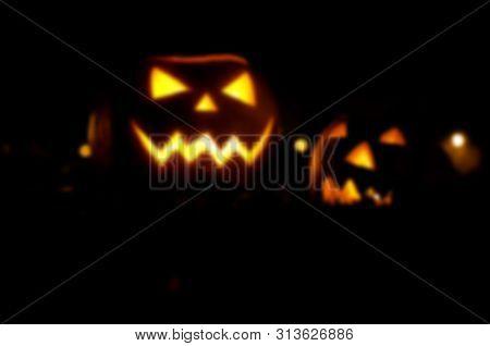 Frightful Ghost Face Glowing On Halloween In The Darkness, Blur. Halloween Pumpkin On Dark Backgroun