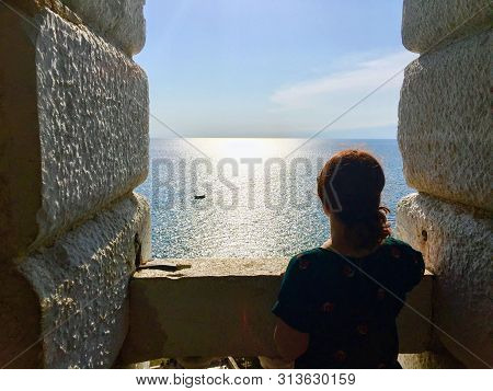 A young woman alone standing from the top of an old stone bell tower looking out at the vast ocean.  This is a top the bell tower in Rovinj, Croatia looking out at the glimmering Adriatic Sea. poster