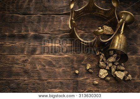 Golden Crown And A Award Cup With A Gold On A Brown Wooden Table Background With Copy Space.