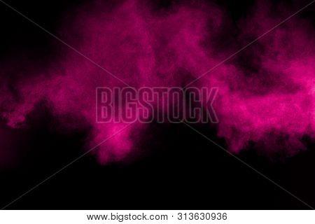 Explosion Of Pink Color Powder On Black Background. Splash Of Color Powder Dust On Dark Background.