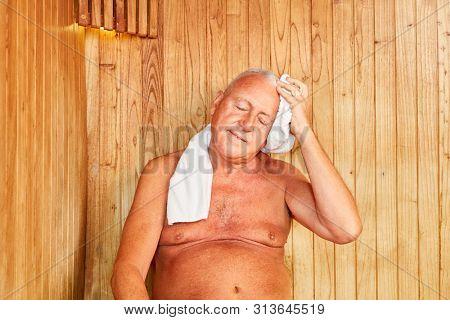 Senior man sweats in the sauna or steam sauna for health