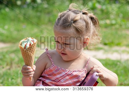 Angry Little Girl Looking At Waffle Horn Of Ice Cream With Bewilderment In The Summer Park