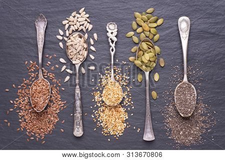 Various seeds - sesame, flax seed, sunflower seeds, pumpkin seed, chia in spoons on a black stone background. Top view
